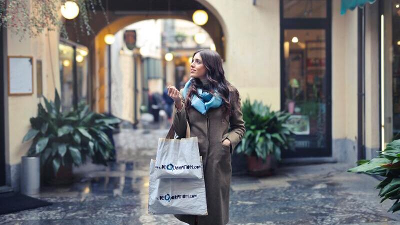 Mulher andando na rua segurando sacolas