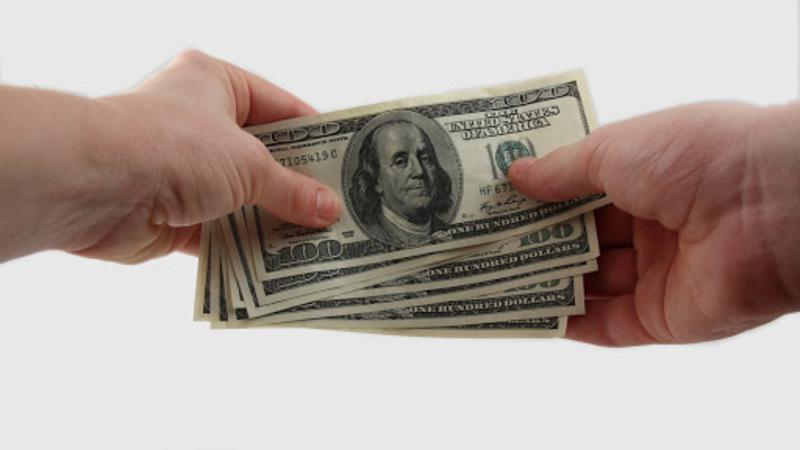 Pessoa segurando nota de dinheiro com as duas mãos