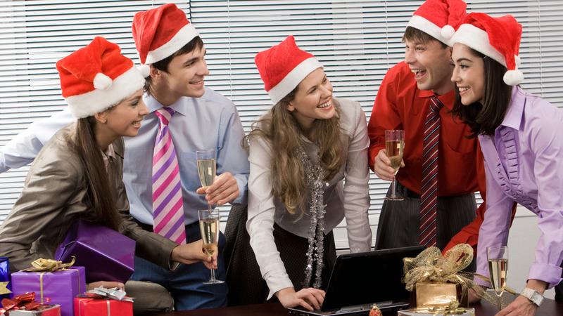 Pessoas no escritório usando gorros de Papai Noel