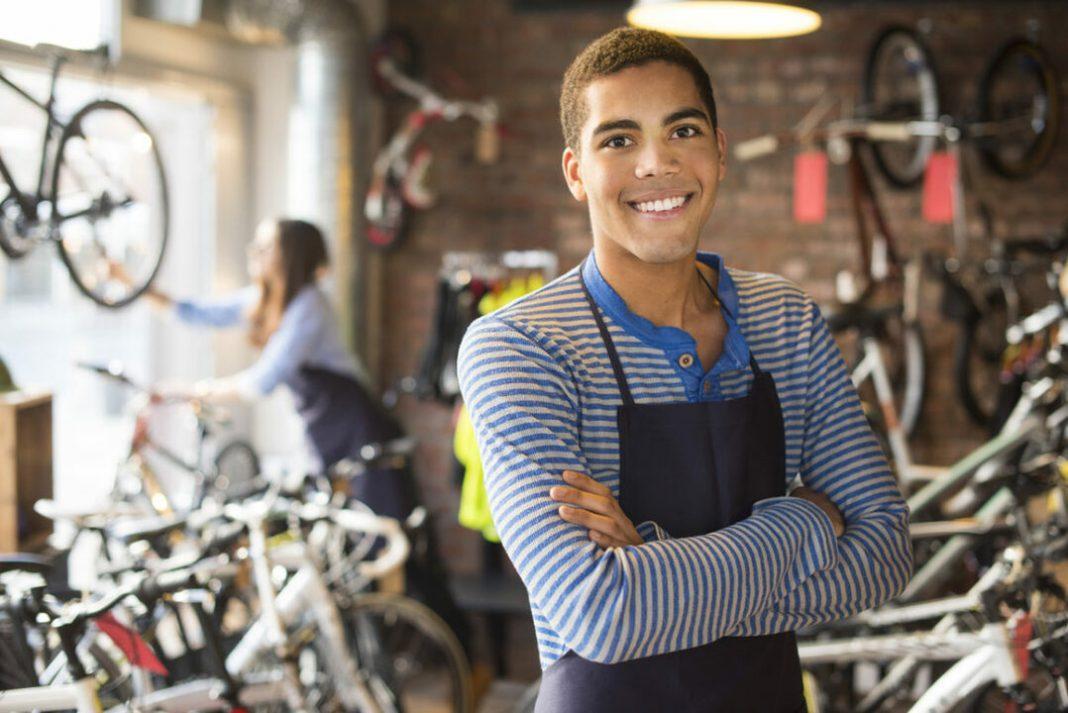 Jovem aprendiz trabalhando em oficina de bicicleta