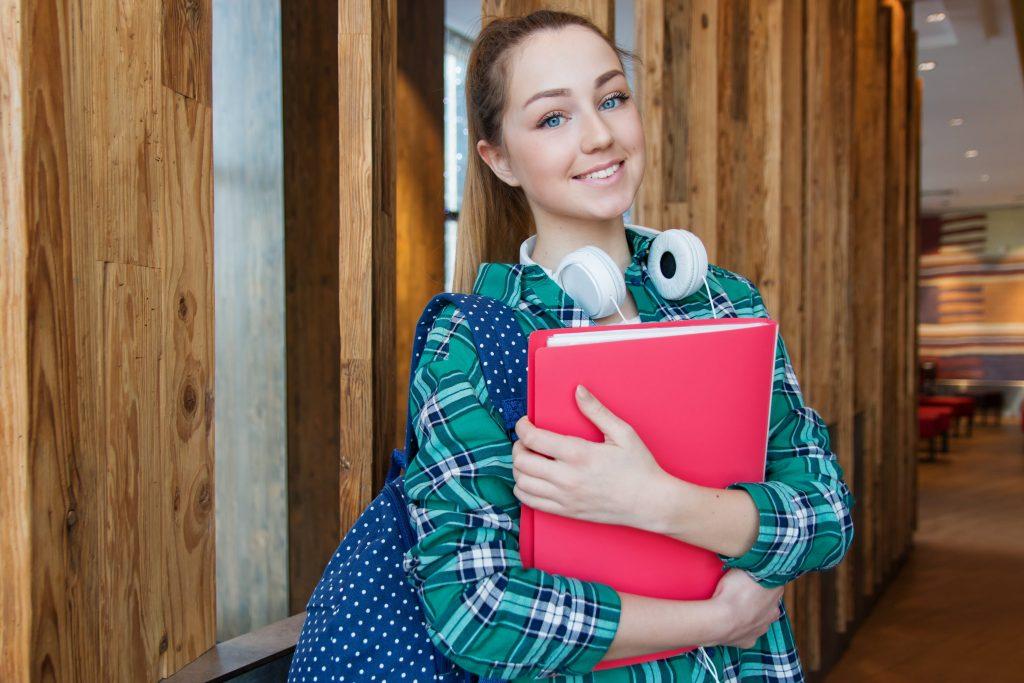 Mulher usando mochila e fones de ouvido segurando pasta vermelha