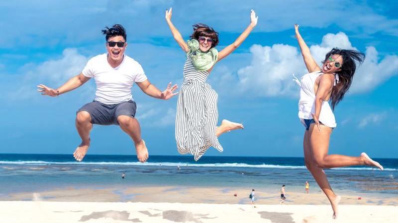 Um homem e duas mulheres alegres pulando na praia