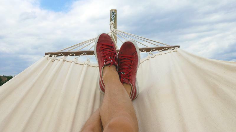 Pernas de pessoa deitada na rede usando tênis vermelhos