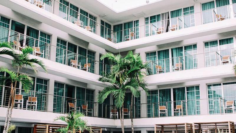 Fachada de hotel, com 3 andares e varandas. Cadeiras vazias, palmeiras à frente