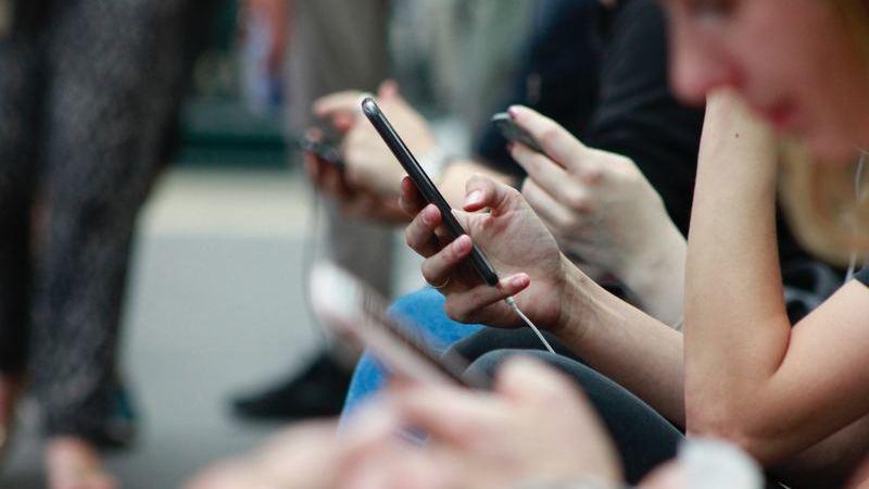 Pessoa em perfil segura telefone celular e desliza pela tela