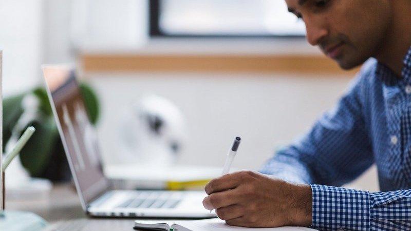 Homem escreve em caderno enquanto olha tela de laptop