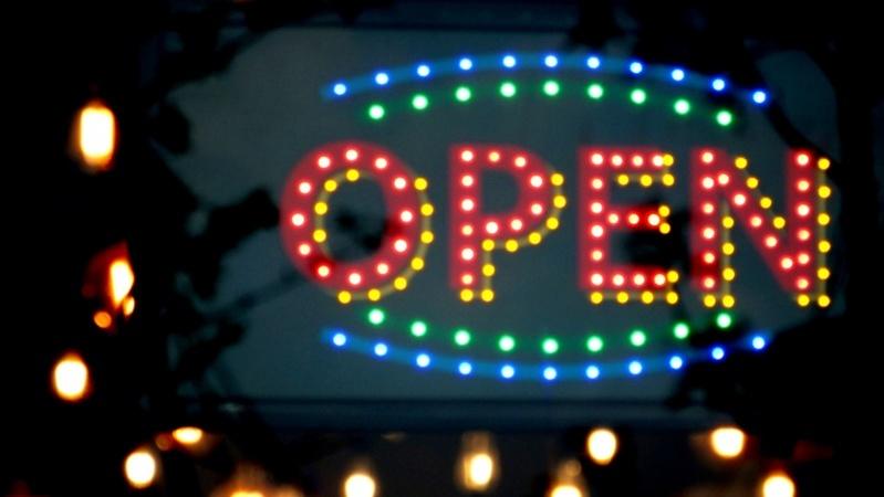 """Sinal de estabelecimento aberto em neon colorido, escrito """"open"""""""