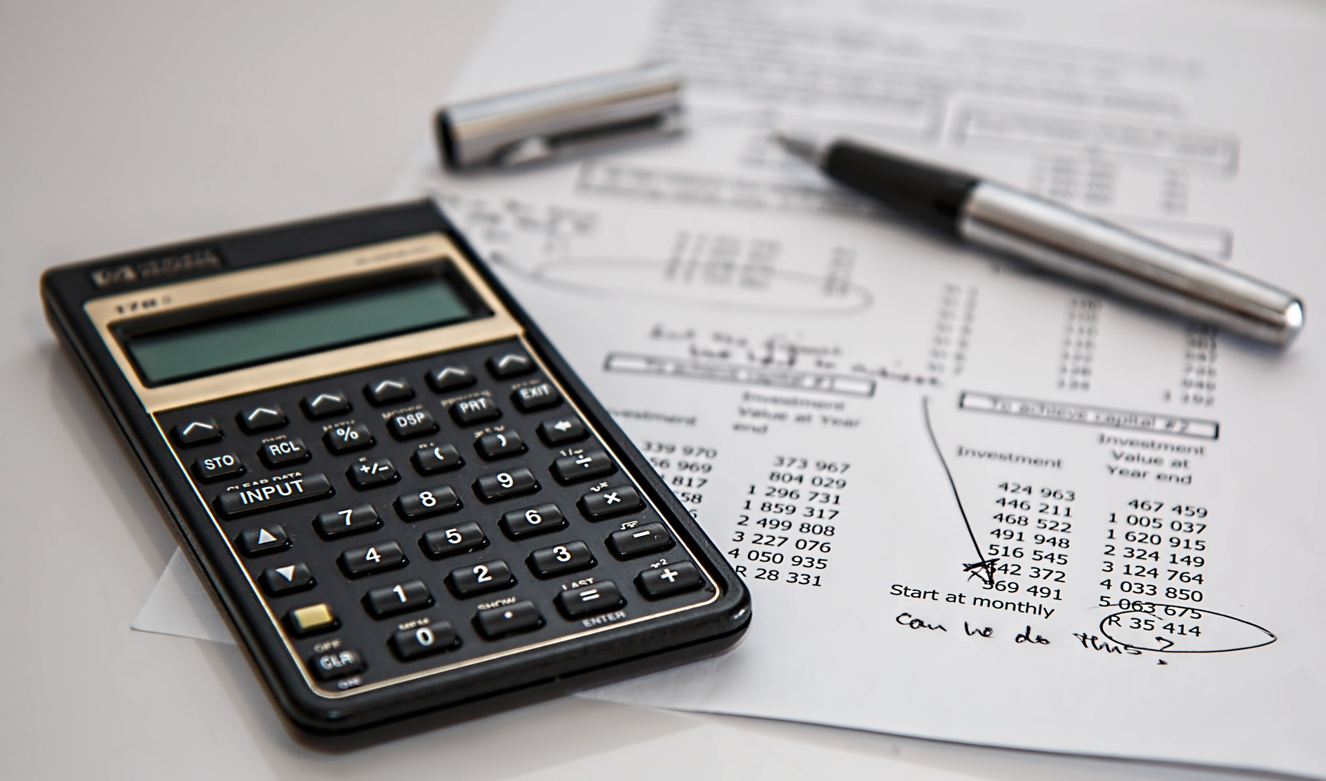 Calculadora, papel e caneta sobre mesa