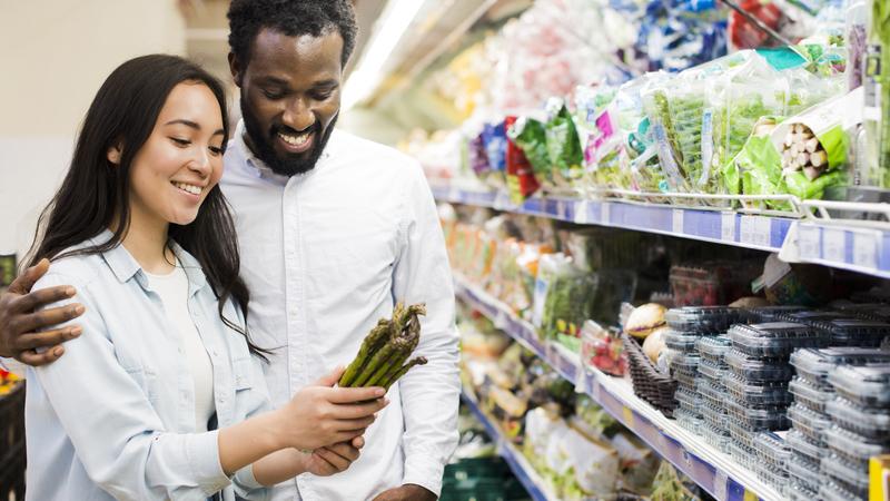 Casal sorrindo em frente prateleira de supermercado. A mulher segura vegetais. O homem abraça a mulher.