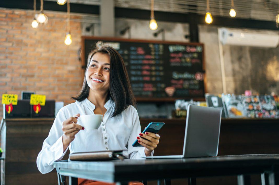 Mulher tomando café e utilizando o celular