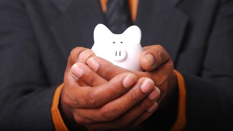 Homem de terno segurando, em suas duas mãos, um cofre branco em formato de porquinho.