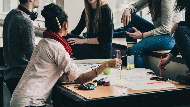 grupo de pessoas em reunião em torno de mesa fazendo anotações