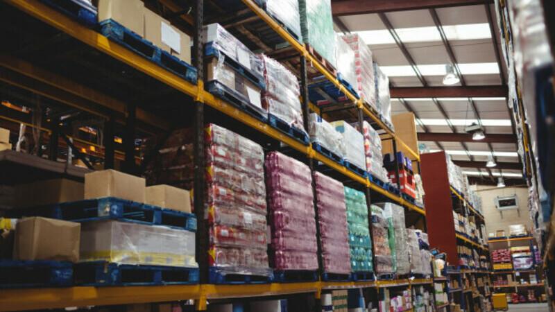 Corredor de um estoque com caixas e produtos embalados em prateleiras grandes