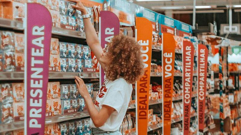Mulher pega produtos em prateleira de supermercado