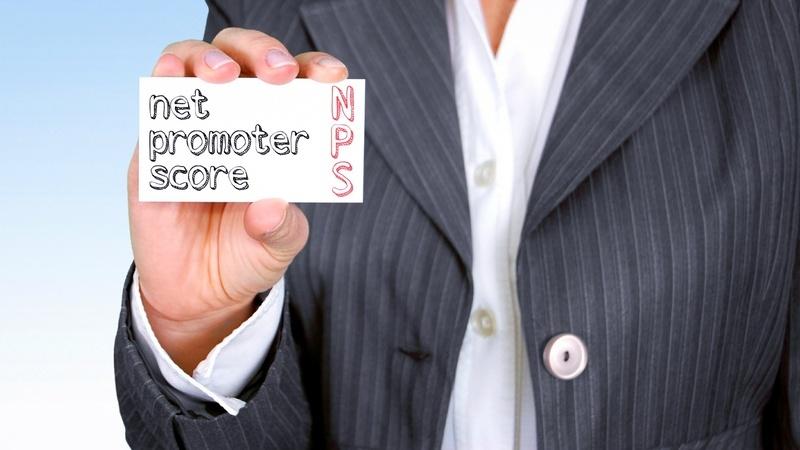 """Pessoa de terno segurando placa branca com o texto """"NPS - Net Promoter Score"""". Não é possível ver o rosto da pessoa."""