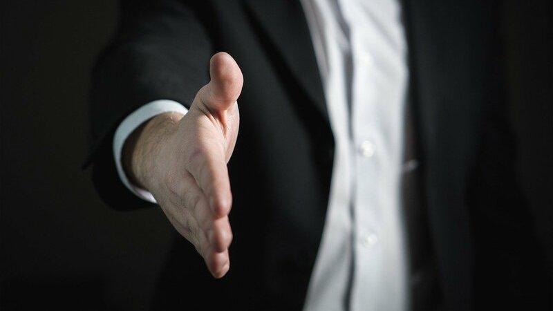 homem estende a mão para cumprimentar