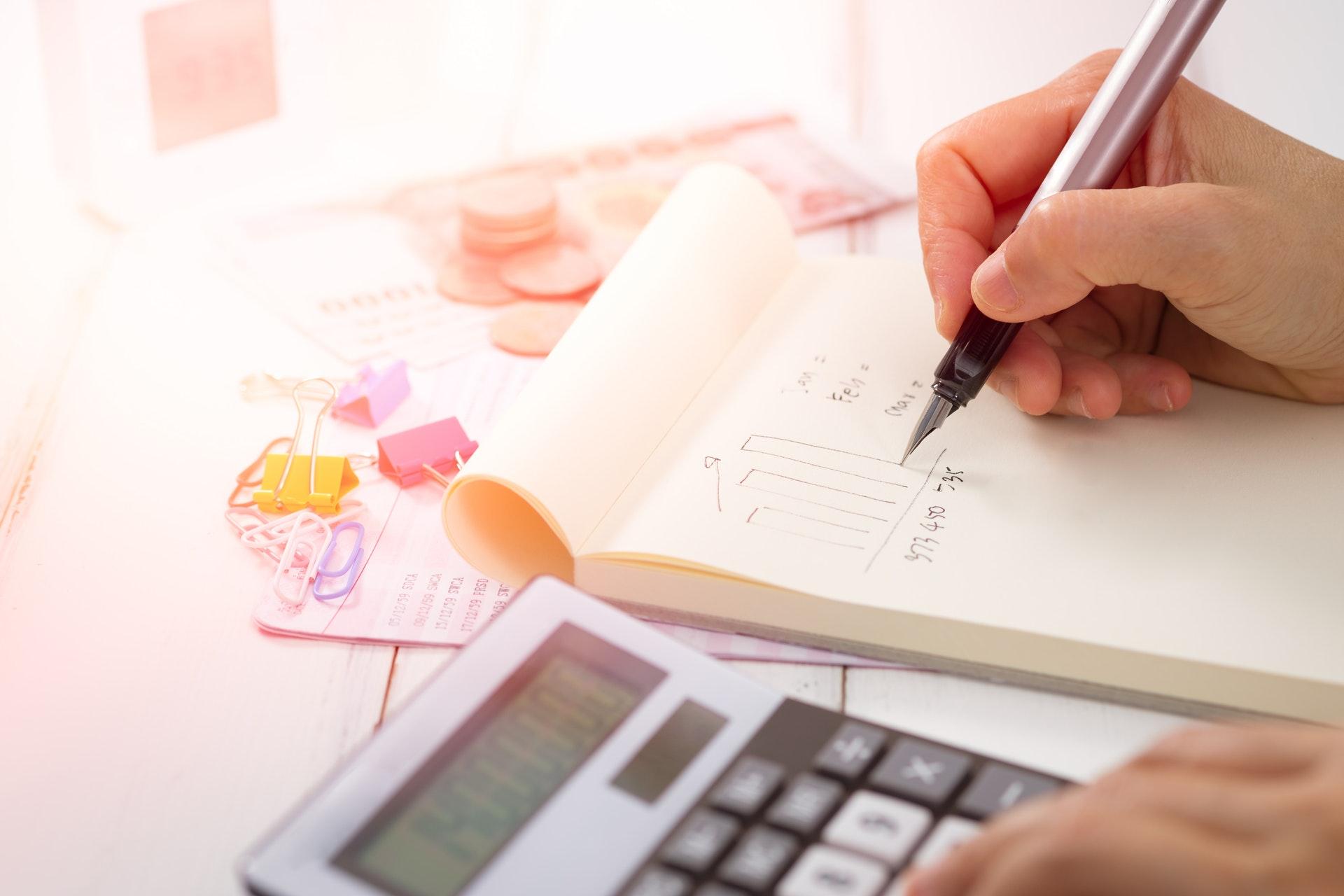 Pessoa fazendo contas usando caneta, bloco e calculadora