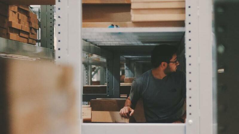 Homem no meio de um estoque de prateleiras e caixas