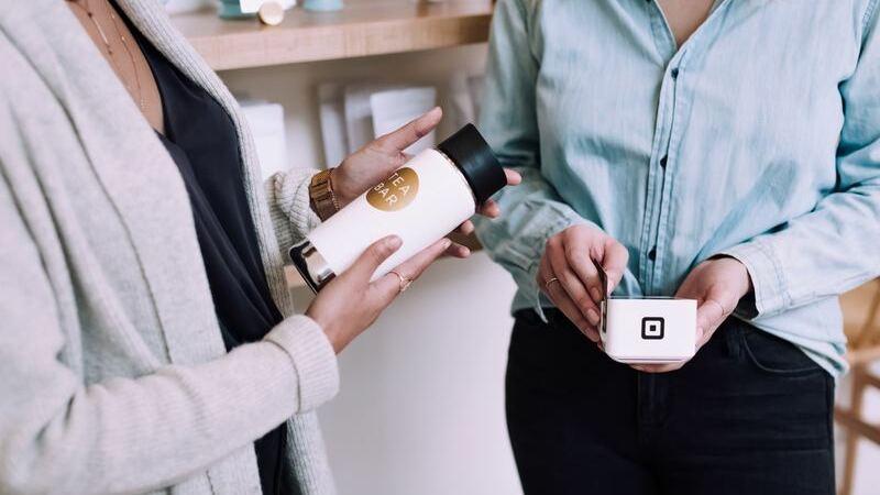 Há 2 mulheres: à esquerda, uma segura um produto similar a um copo. À direita, vendedora passa cartão de crédito na máquina