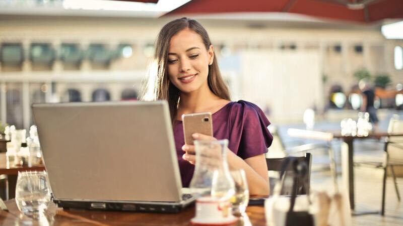 Em uma cafeteria, há uma mulher sorrindo e segurando smartphone em frente a notebook aberto.