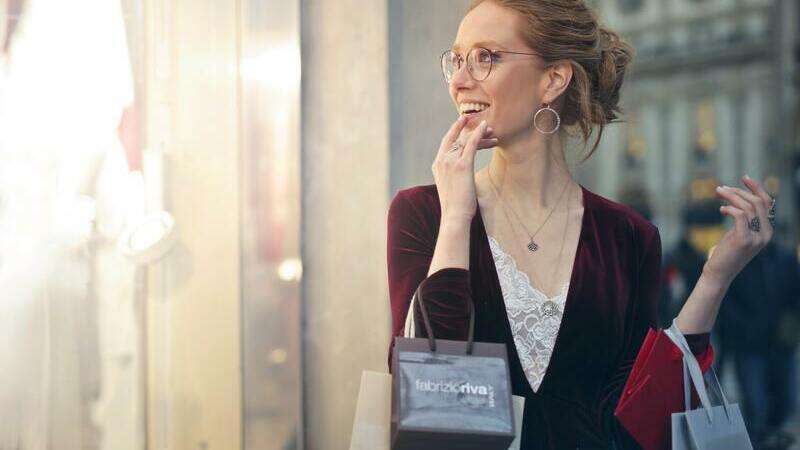Mulher segurando sacolas de compras olhando para vitrine e sorrindo.