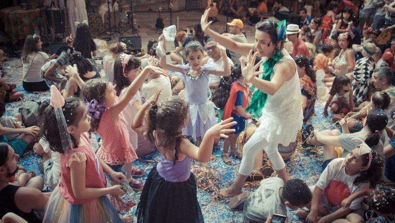 Roda de crianças fantasiadas para o carnaval lideradas por uma mulher vestida de branco e verde usando um microfone.