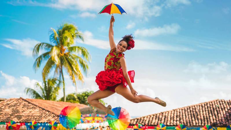 Dançarina de frevo executando um passo de dança segurando um guarda-chuva ao ar livre.