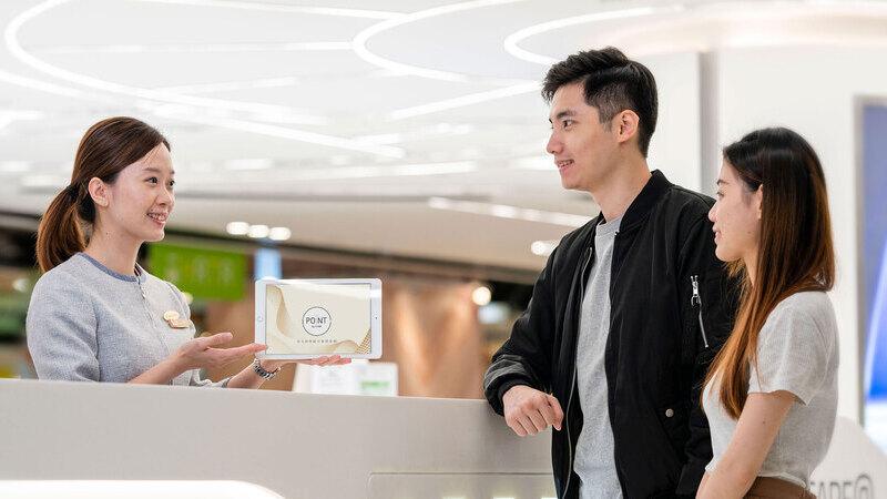 Profissional segurando tablet e apresentando produto para casal em balcão de loja.