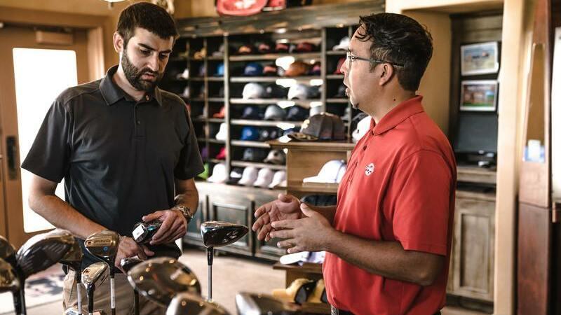 Vendedor de loja esportiva atendendo o cliente perto de tacos de golfe. Há no fundo boinas e chapéus em uma prateleira.