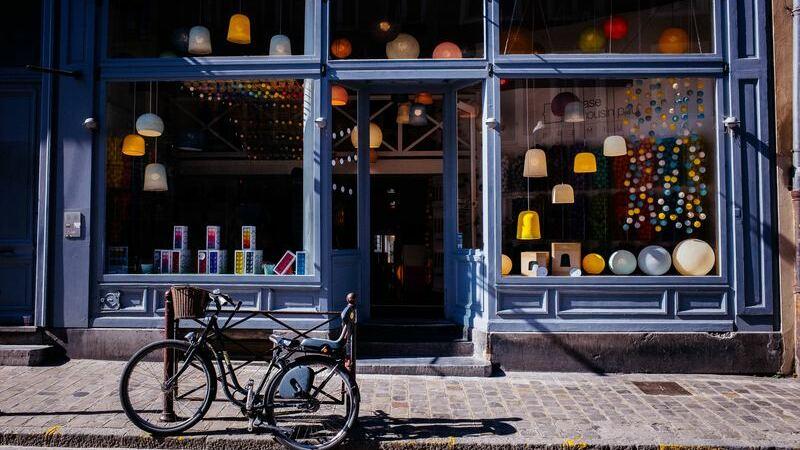 Frente de loja azul com bicicleta estacionada na frente. Loja mostra luminárias amarelos, azuis e brancos.