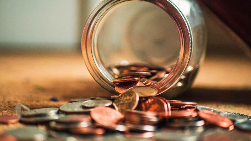 Pote de vidro virado, no chão, com moedas dentro e fora.
