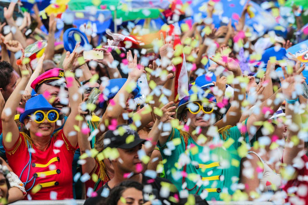 Em um bloco de carnaval, há confetes caindo sobre as pessoas. Elas estão fantasiadas usando óculos e chapéus coloridos.