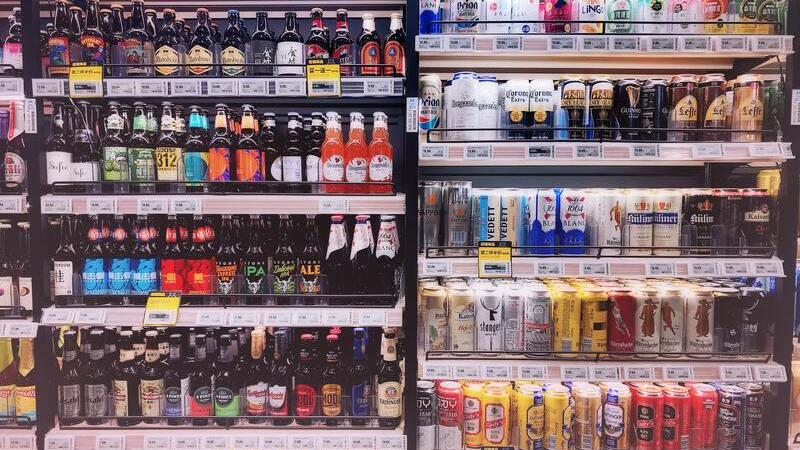 Refrigerador aberto de supermercado com bebidas com latas e garrafas coloridas