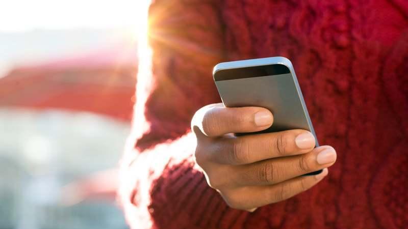 Pessoa com blusa de frio de linho vermelha, segurando um smartphone com uma de suas mãos.