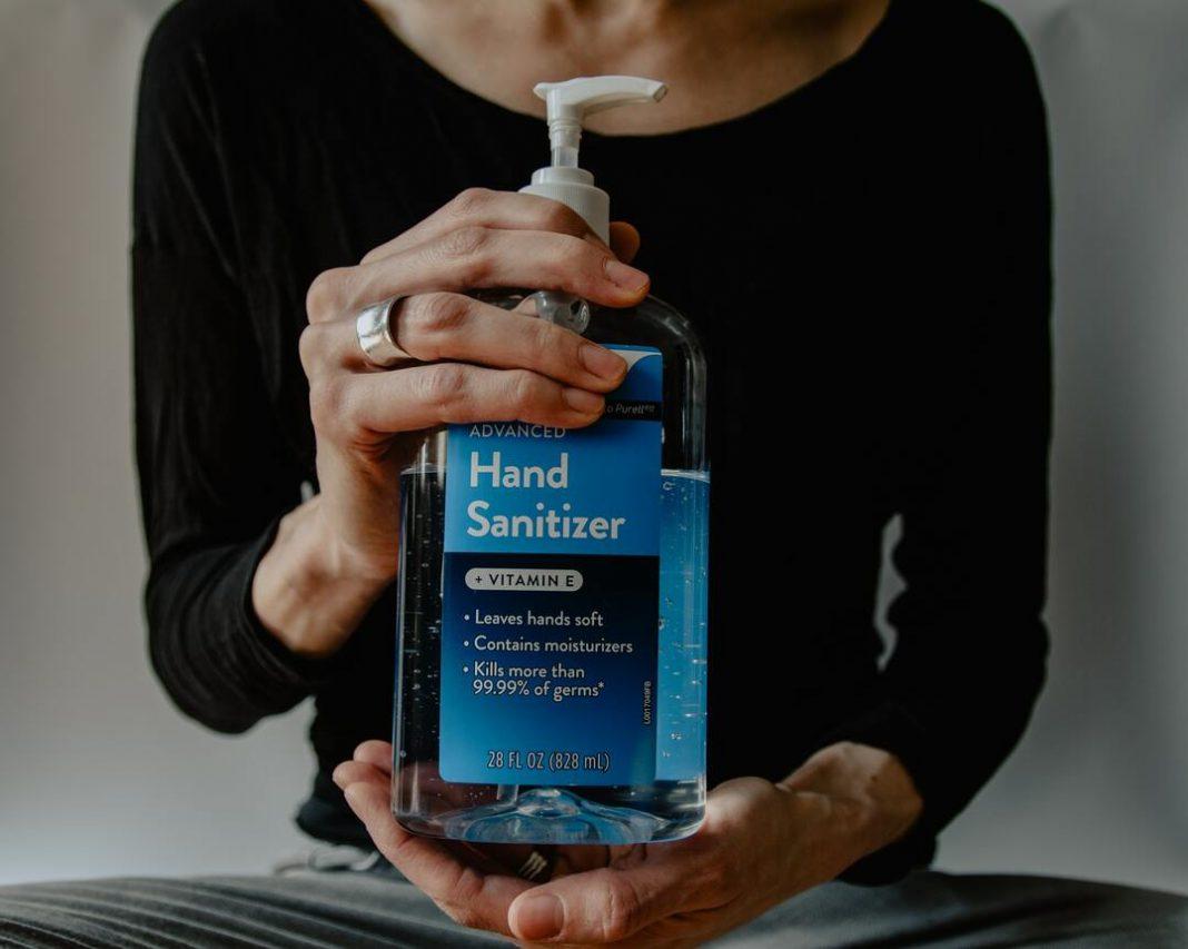Pessoa segurando, com as duas mãos, um vidro de álcool em gel de 800ml.