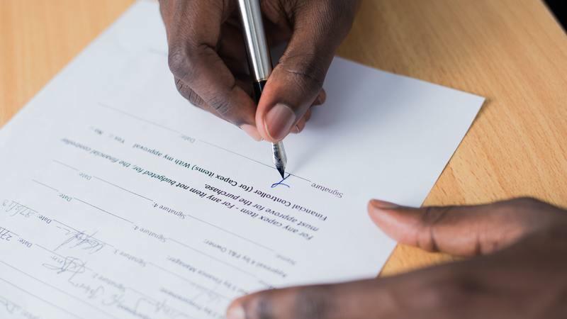 A imagem apresenta as mãos de uma pessoa assinando um papel.