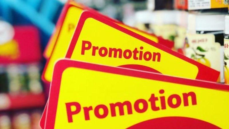 Placa de promoção nas cores amarelo e vermelho na prateleira do supermercado.