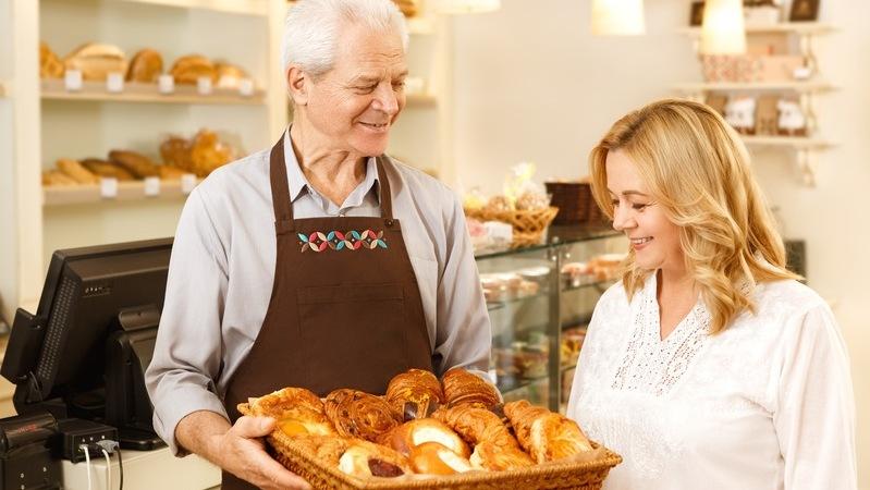 Homem de avental segurando bandeja de pães, mulher sorrindo e escolhendo um dos pães da bandeja.