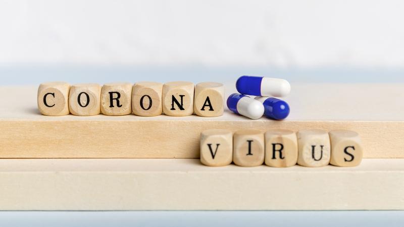 Pecinhas em madeira, cada uma com uma letra, formam a palavra coronavírus. Há também três comprimidos de remédios coloridos.