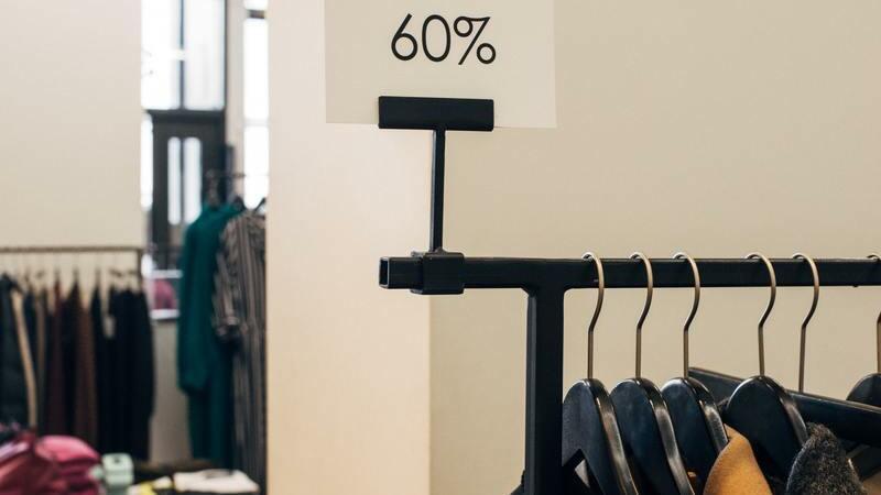 Imagem com uma arara com casacos pendurados em uma loja de roupas. Logo acima dela, uma placa com o texto de 60% de desconto.
