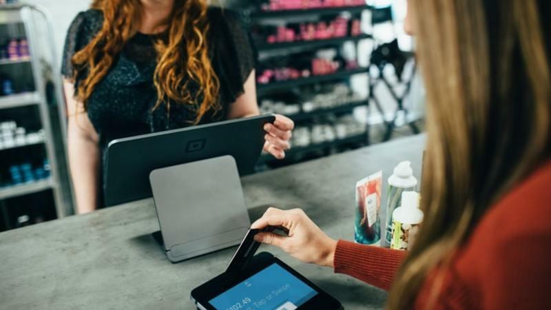 Uma mulher de frente ao balcão do caixa da loja passando cartão de crédito na máquina. A atendente mexe na tela do tablet.