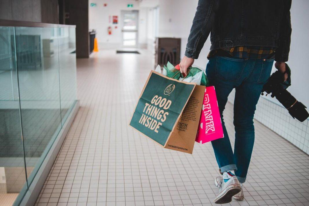 A imagem mostra uma pessoa de costas segurando sacolas de compras e uma câmera fotográfica.