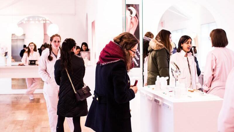 Várias mulheres em uma loja de maquiagem. Algumas conversam, outras veem a prateleira com os produtos.