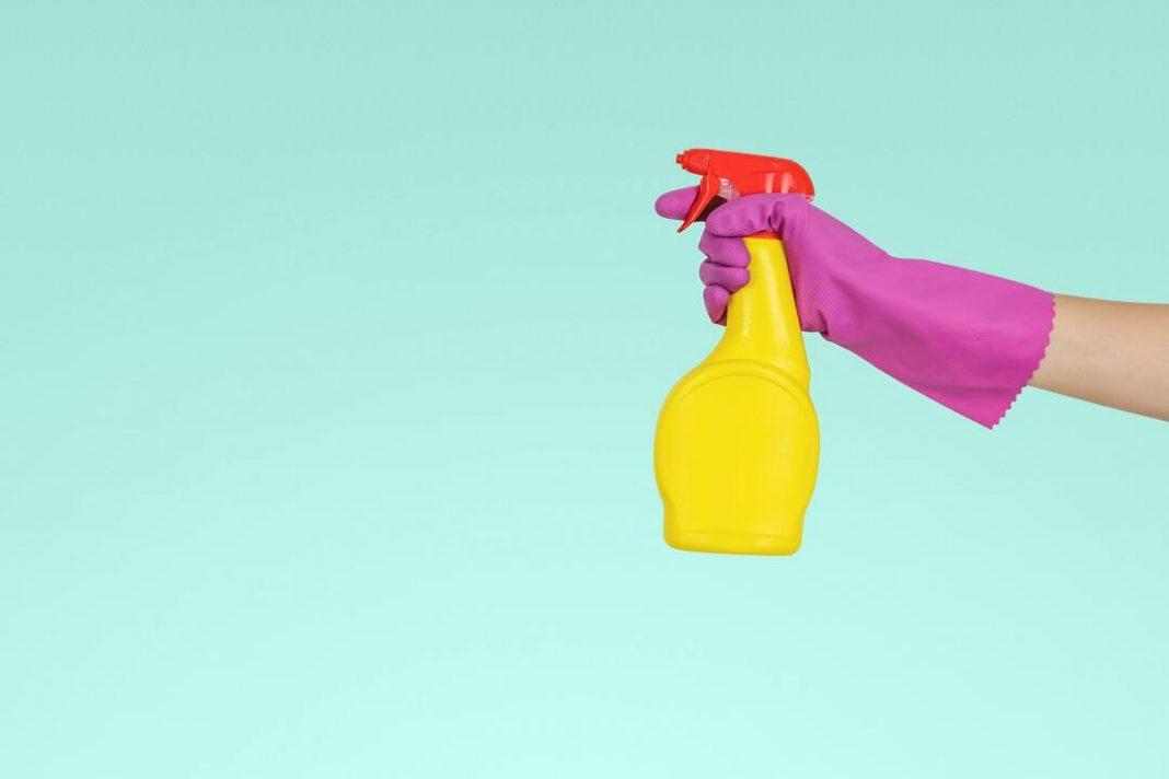 Em um fundo chapado azul, uma mão com luvas segura um borrifador amarelo.