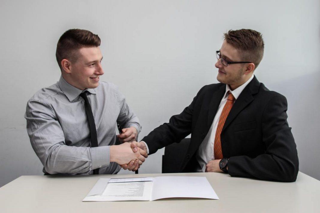 Dois homens se olhando e sorrindo enquanto apertam as mãos. Parecem ser dois empresários fechando um negócio.