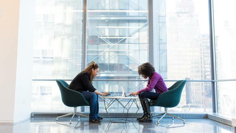 Duas mulheres sentadas, uma de frente para a outra, usando tablets apoiados sobre mesa.