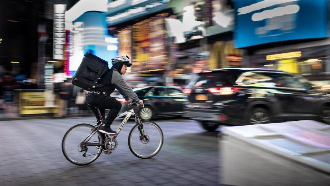 Entregador de bicicleta em rua movimentada. Ao fundo comércio e carros desfocados.