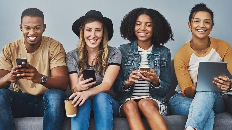 Quatro jovens da geração z sentados em um sofá sorrindo para câmera e segurando smartphones e cafés.