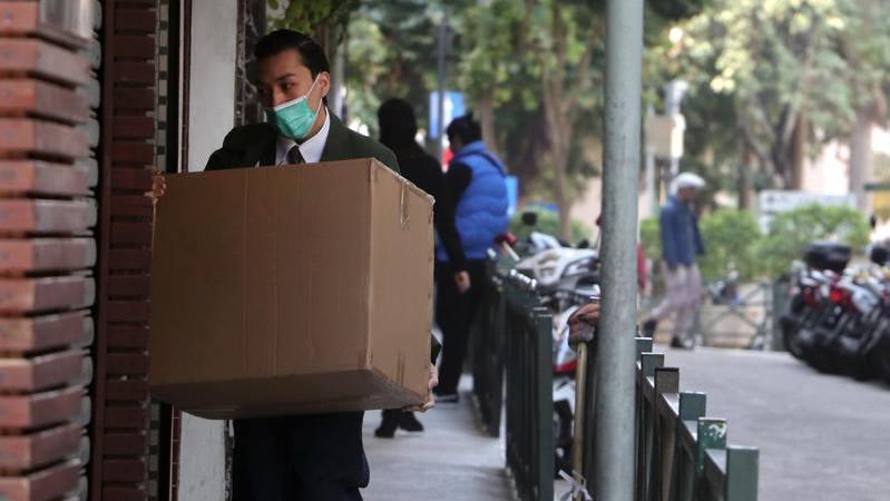Um homem usando terno e máscara segura uma caixa de papelão em uma via pública.