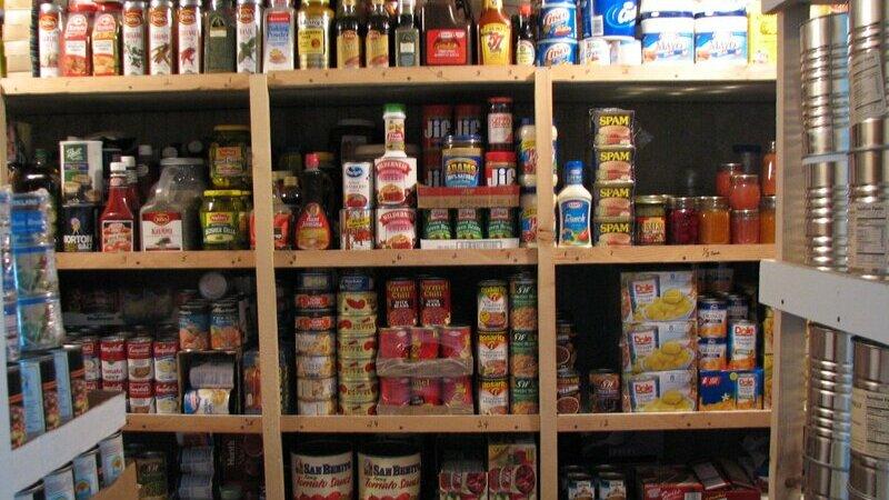 Estante de madeira com diversos produtos alimentícios em um estoque.